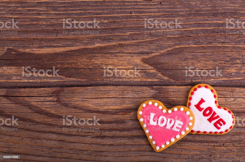 Gingerbread cookies with icing heart shaped on wooden table. 스톡 사진