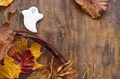 istock Gingerbread ghost for halloween, decorated with autumn leaves, on a wooden background. 867176028