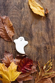 istock Gingerbread ghost for halloween, decorated with autumn leaves, on a wooden background. 867176494
