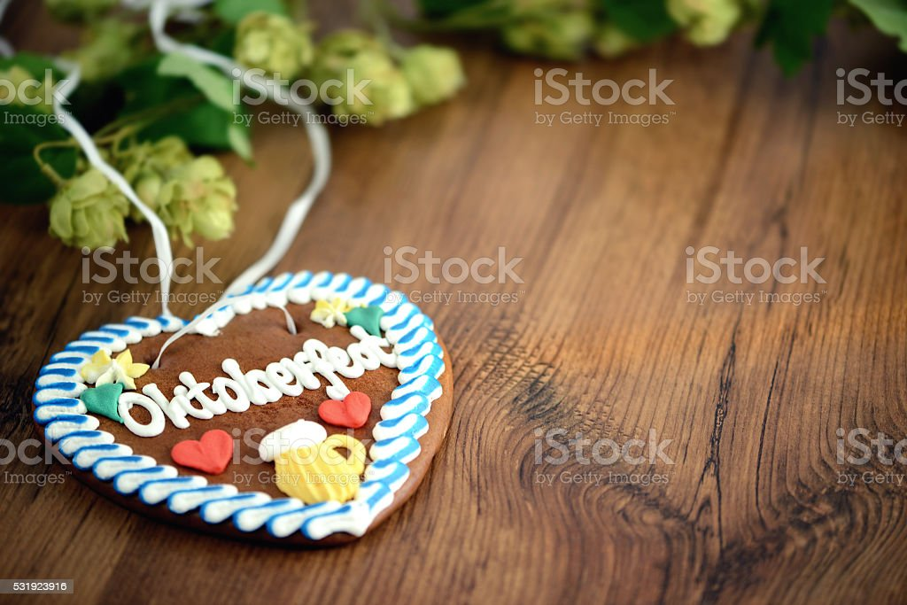Gingerbread heart on wooden table with hop copy space. Oktoberfest stock photo