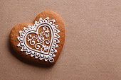 Decorative heart cookie on textured paper background.
