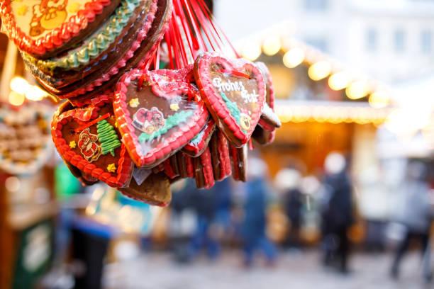 lebkuchenherzen auf deutschen weihnachtsmarkt. nürnberg, münchen, berlin, hamburg weihnachtsmarkt in deutschland. cookies geschrieben happy holiday genannt auf traditionellen lebkuchen lebkuchenherz in deutscher sprache - christkindlmarkt stock-fotos und bilder