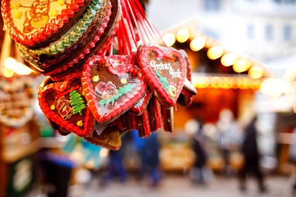 lebkuchenherzen auf deutschen weihnachtsmarkt. nürnberg, münchen, berlin, hamburg weihnachtsmarkt in deutschland. auf traditionellen lebkuchen sogenannte cookies geschrieben frohe chrismtas lebkuchen in deutscher sprache - weihnachtsfeier münchen stock-fotos und bilder