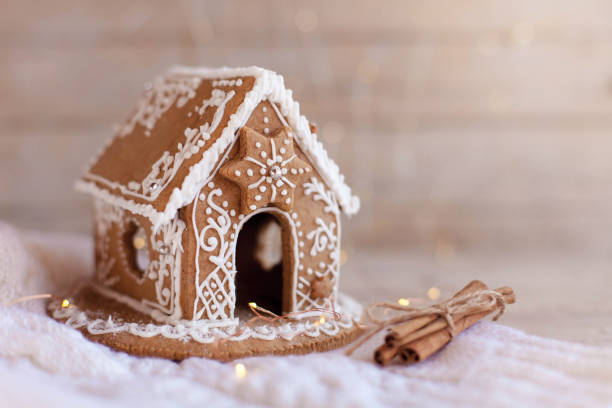 Gingerbread house, Christmas cozy decorations on wooden and knitted background with glares. stock photo