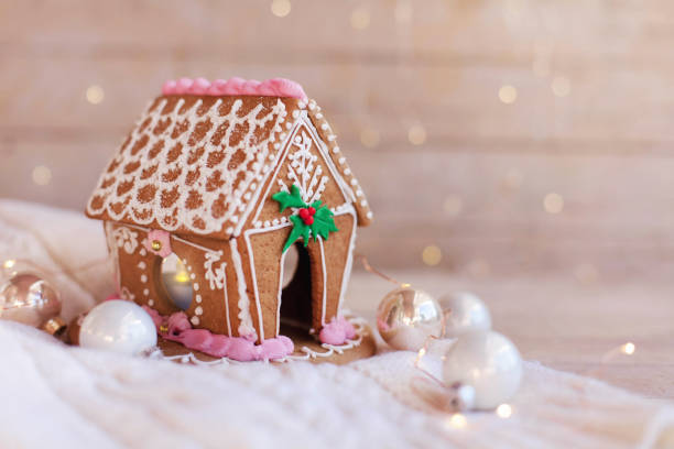 Gingerbread house, Christmas decorations on wooden background with glares. Homemade sweets stock photo