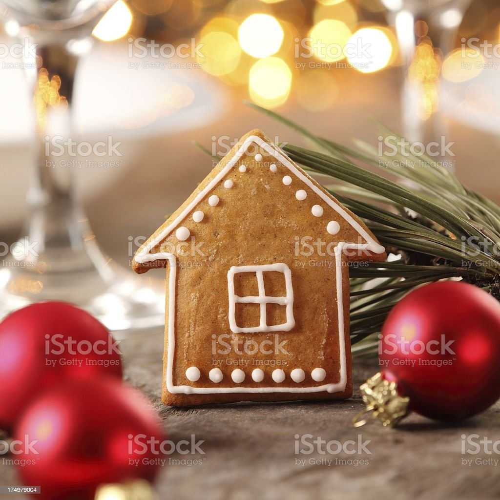 Gingerbread house cookie and red bulbs laying on a table stock photo