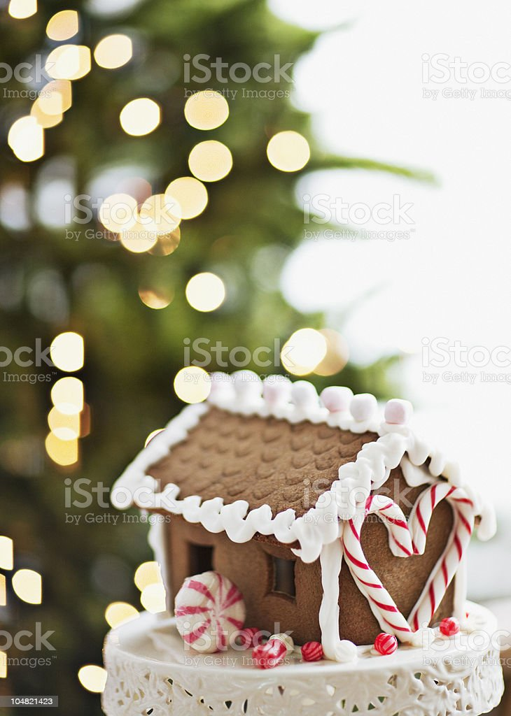 Gingerbread house in front of Christmas tree stock photo