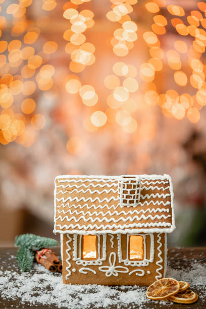Gingerbread house on table. Defocused lights of Christmas garland. Morning in the bright living room. Holiday mood. Figure deer stock photo