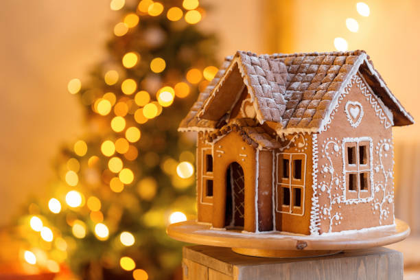 gingerbread house over defocused lights of Chrismtas decorated fir tree stock photo