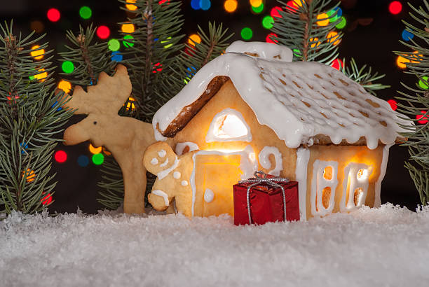 Gingerbread house with gingerbread man, elk and christmas trees stock photo