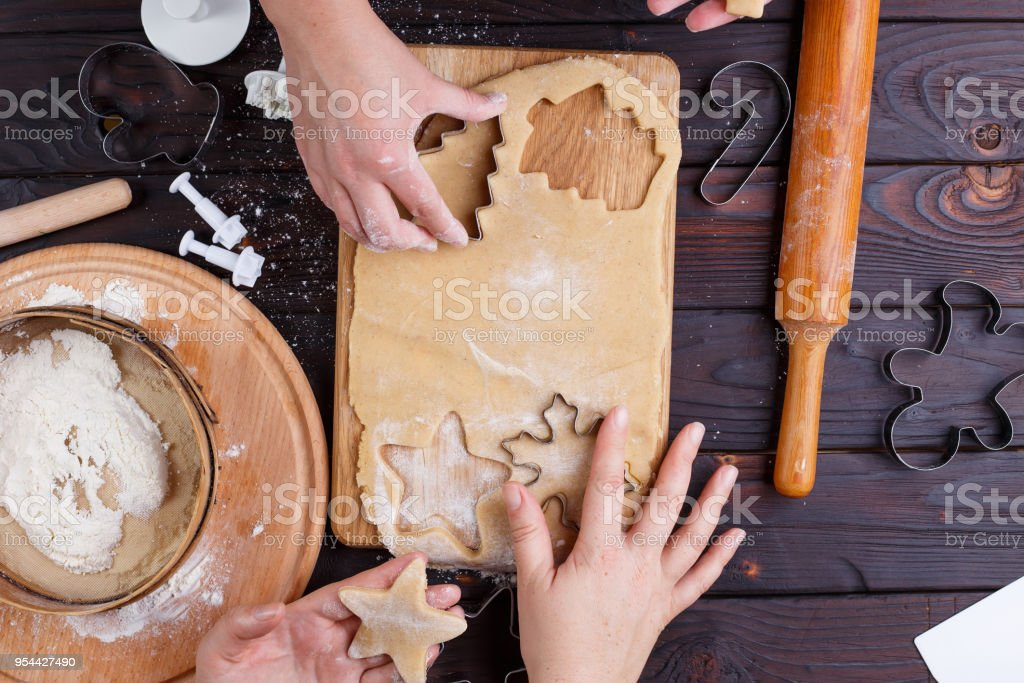 Gingerbread making. Friends cutting cookies of gingerbread dough stock photo
