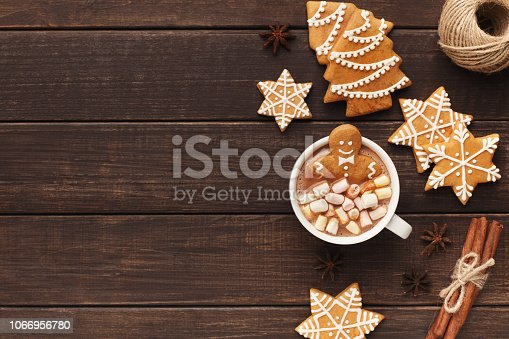 Cozy Christmas composition. Gingerbread man bathing in cup of hot cocoa with marshmallows, copy space, top view