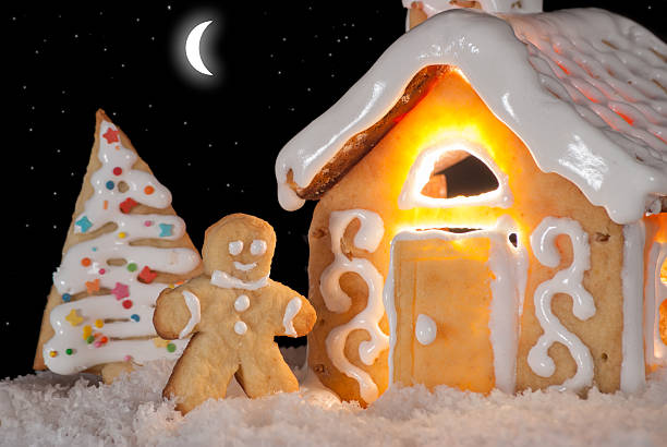 Gingerbread man cookie standing in snow beside house stock photo