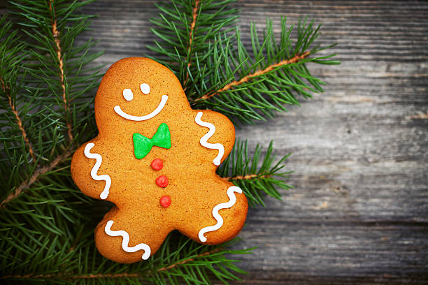 Gingerbread man lying on a pine branch on a wooden surface stock photo