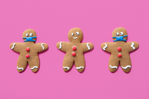 A holiday classic, the gingerbread man Christmas cookie wears frosting PPE to protect himself and prevent the spread of Covid-19 / Coronavirus during the viral global pandemic of 2020.  One cookie is not wearing a mask and the other look at him from the corner of their frosting eyes.