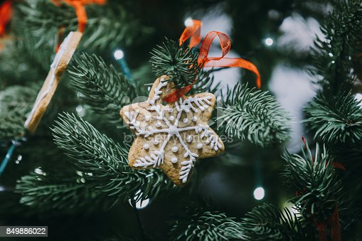 istock Gingerbread snowflake hanging on decorated Christmas tree 849886022