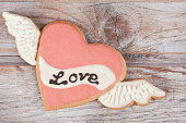 Gingerbread Valentine's cookie with icing heart shaped on wooden rustic table.