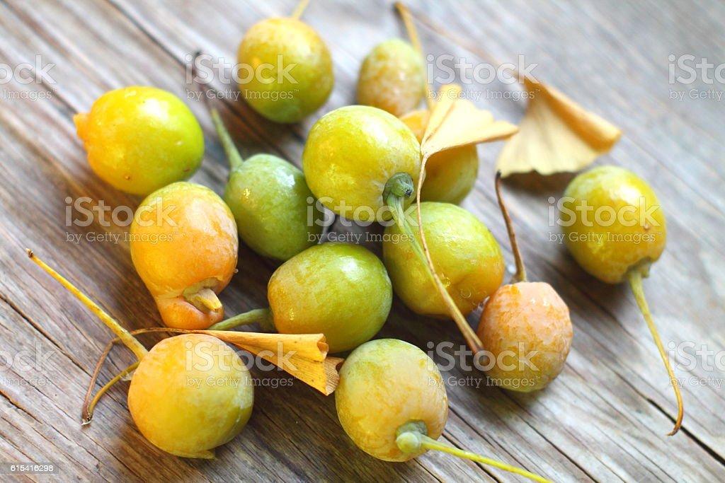 Ginkgo bilboa fruits on woody table desk. stock photo