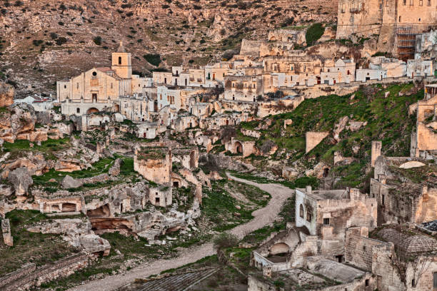 Ginosa, Taranto, Puglia, Italy: landscape of the old town Ginosa, Taranto, Puglia, Italy: landscape of the old town with the ancient church and the cave houses carved into the tufa rock tuff stock pictures, royalty-free photos & images