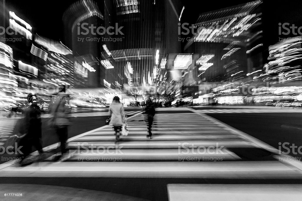 Pedestrians cross the street at the heart of Ginza District in Tokyo....