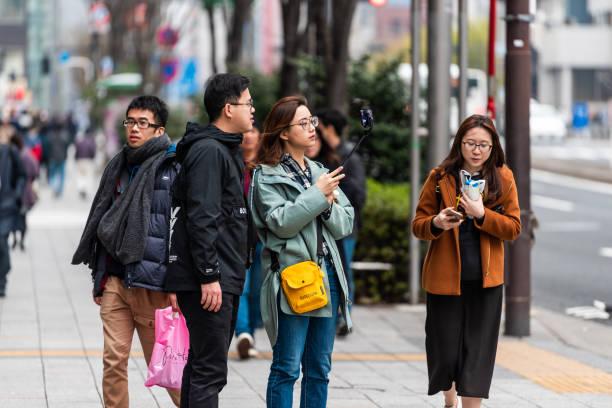 Distrito de Ginza com os turistas na rua do passeio que toma o retrato do selfie com vara - foto de acervo