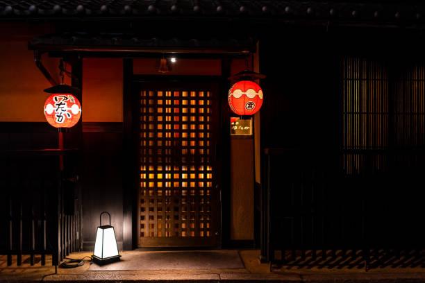 Gion at night illuminated red hanging paper lanterns at entrance to upscale restaurant izakaya in machiya house building stock photo