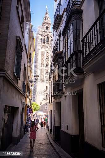 Tourists walk through a narrow street and enjoy the spectacular view of The Giralda - the bell tower of Seville Cathedral in Seville, Spain. It was built as the minaret for the Great Mosque of Seville.