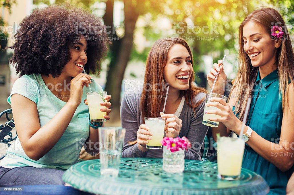 Girfriends having iced drinks in cafe stock photo