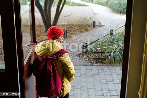 1045032684 istock photo Girl 12 years old schoolgirl leaving the house with a backpack opening the door 1201372495