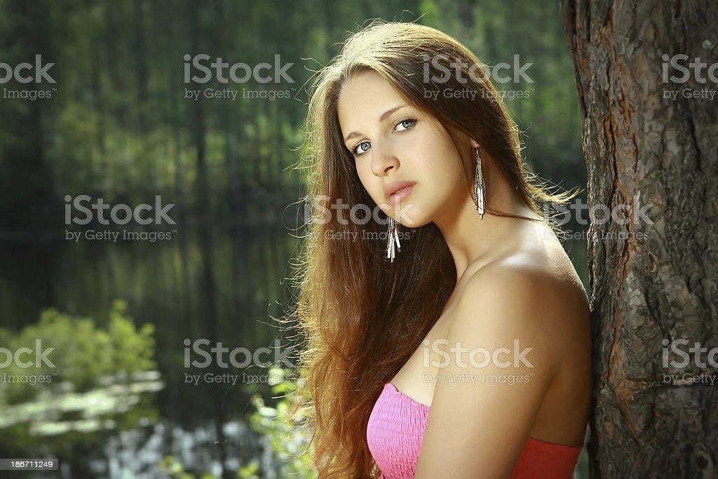 Fille, 16 ans, en robe rose, au bord du lac. - Photo