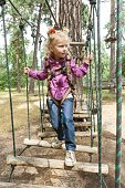 Girl 4, 5 years old in adventure climbing high wire park, active lifestyle of children.