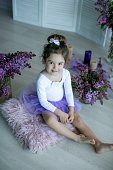 Girl 4-6 years old sitting on a pillow in a purple skirt surrounded by lilac flowers.