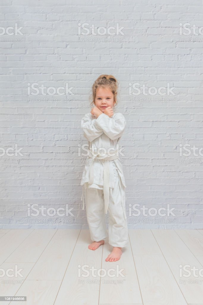 the girl, a child in a kimono on karate training works out blows and...