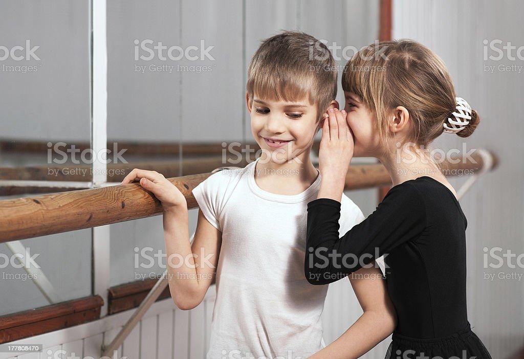 girl a word in one's boy's ear near barre stock photo