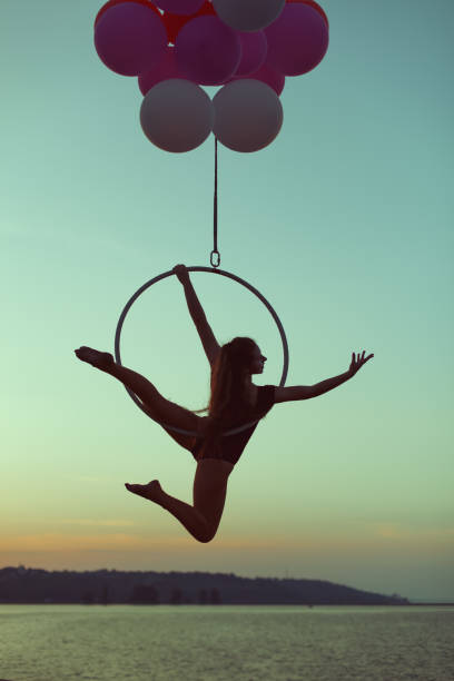 girl acrobat hovers in the air on the balloons. - equilibrista foto e immagini stock
