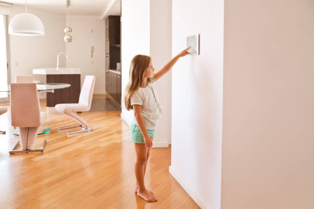 Girl activating smart home security system Girl activating smart home security system. The control panel is installed in the apartment on the wall. smart thermostat stock pictures, royalty-free photos & images