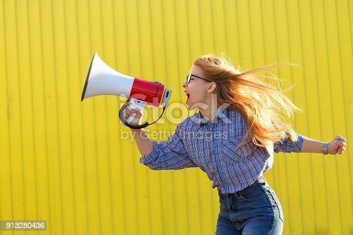 istock Girl activist shouts in loudspeaker 913280436