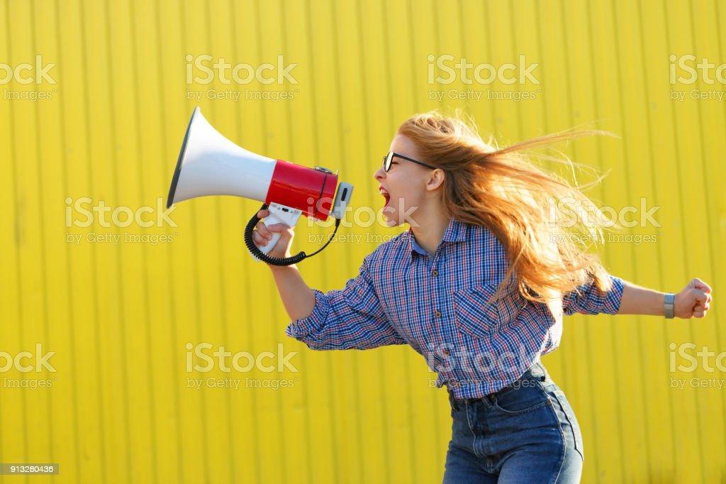 Girl activist shouts in loudspeaker stock photo