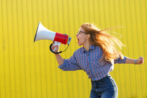 Girl activist shouts in loudspeaker Young attractive girl activist in shirt yelling into loudspeaker. A single picket. Active life position. The struggle for women's rights women's rights stock pictures, royalty-free photos & images