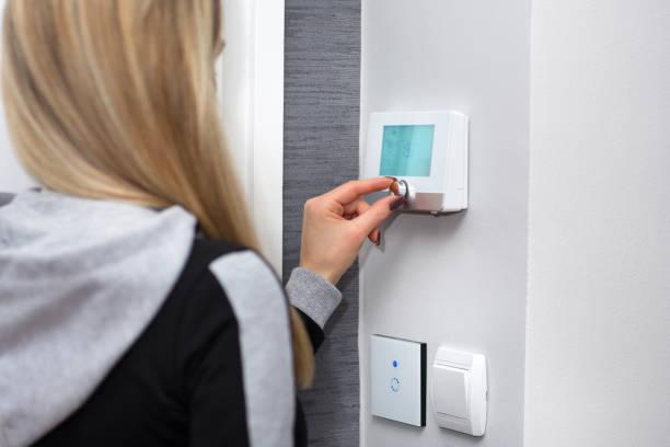 flickan justerar och reglera rumstemperaturen på smart switch - kvinna ventilationssystem bildbanksfoton och bilder
