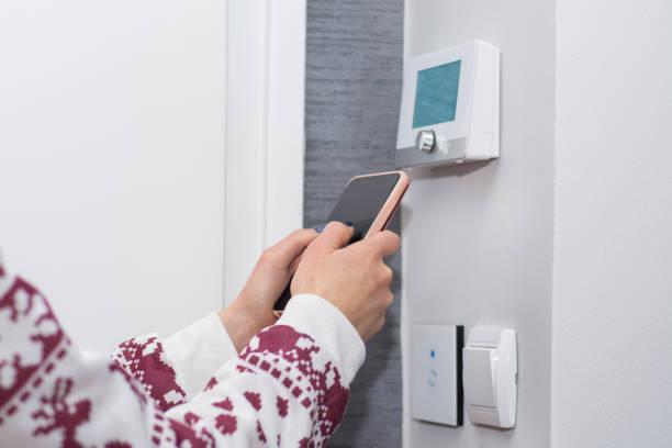 flickan justerar och reglera rumstemperaturen med smart telefon på switch vägg - kvinna ventilationssystem bildbanksfoton och bilder