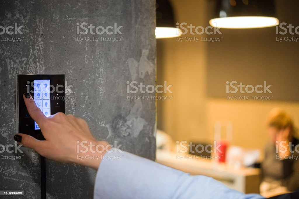 Mädchen passt die Beleuchtung in den Raum mit einem Touch-Schalter – Foto
