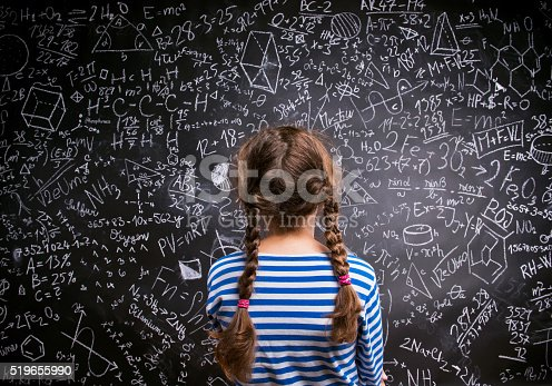 istock Girl  against big blackboard with formulas, back view 519655990