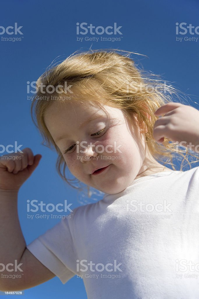 """girl against blue sky, showing her strength """"4 year old girl at the beach, showing how strong she is."""" Active Lifestyle Stock Photo"""