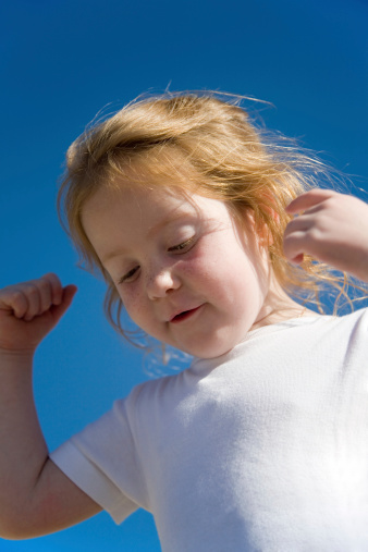Girl Against Blue Sky Showing Her Strength Stock Photo - Download Image Now