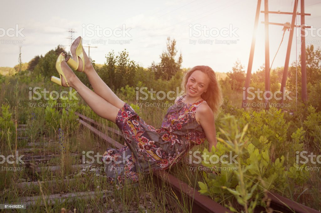 Girl against the evening sunset. A joyful woman looks to the future against the backdrop of a warm past. stock photo