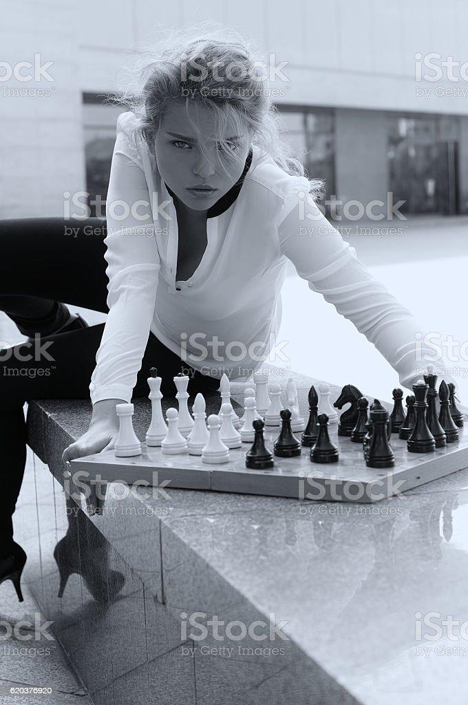 Girl aggressively playing chess zbiór zdjęć royalty-free