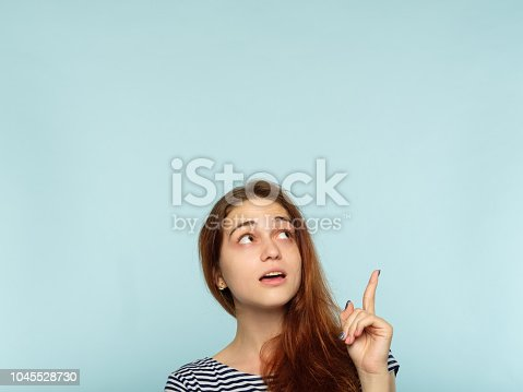 1045527172 istock photo girl amazed point finger advertising space above 1045528730