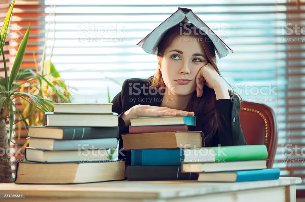 Girl among books stock photo