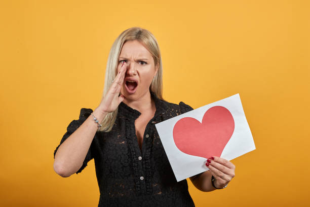 girl an irritated angry woman screams nervously holding piece of paper red heart Beautiful blonde girl in black dress on yellow background an irritated angry woman screams nervously holding piece of paper with red heart alas stock pictures, royalty-free photos & images